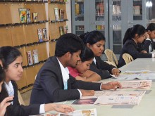 CMR Students studying a Newspaper at the library